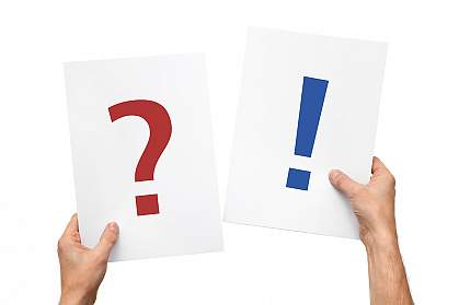 Hands holding up two cards - one displaying a large question mark and the other an exclamation mark.