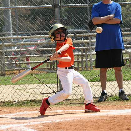Little League batter hitting the ball.