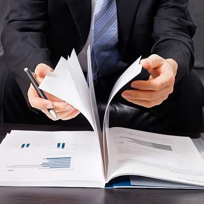 A business man flipping through a report.