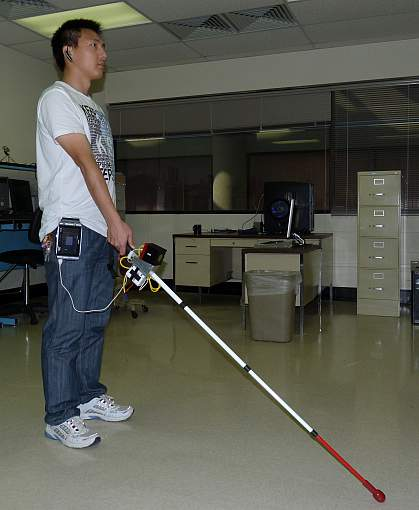 Image of a person holding a prototype co-robotic cane for the visually impaired