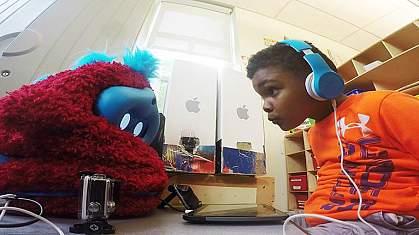 Image of a preschooler interacting with a social robot