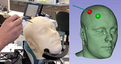 the image shows a hand holding a long thin device against a white mannequin head as well as a computer rendering of the head with the digital trackers.