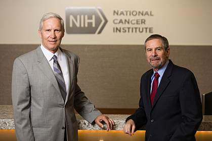 John T. Schiller and Douglas R. Lowy standing in front of the NCI logo