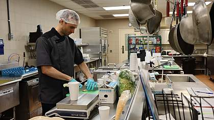 A man chops vegetables in a hospital kitchen.