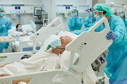 Healthcare worker wheeling hospital bed with senior COVID-19 patient on ventilator