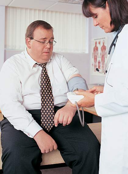 a photo of an obese man having his blood pressure taken by a doctor