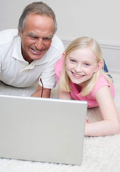 Picture of a grandfather assisting his son and grandson at the computer