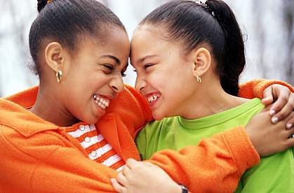Two young African American girls smiling at each other