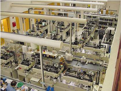 Bird's-eye view of large room with several people working on DNA sequencing equipment