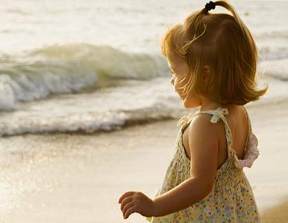 Picture of a little girl standing by the ocean