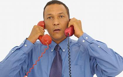 Picture of a man listening to two phones at the same time