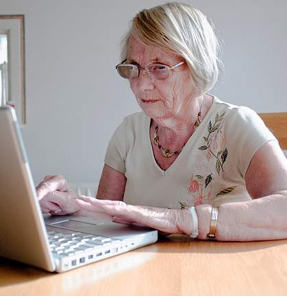 Photo of an older woman reading from her laptop