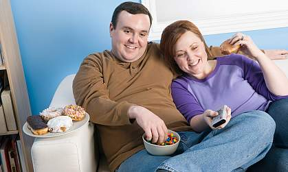 An overweight couple on the sofa eating popcorn.