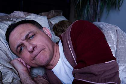 Photo of an angry man lying awake in bed