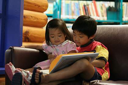 a photo of two preschool-age children looking at a book