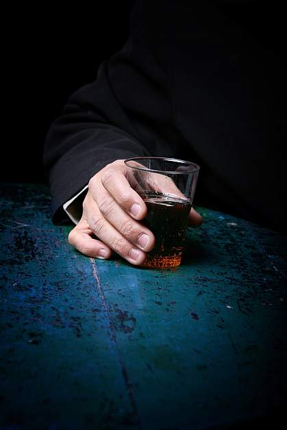 Photo of a hand holding a glass with an alcoholic drink