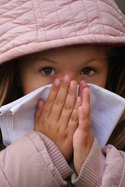 Photo of a child in a winter coat blowing her nose