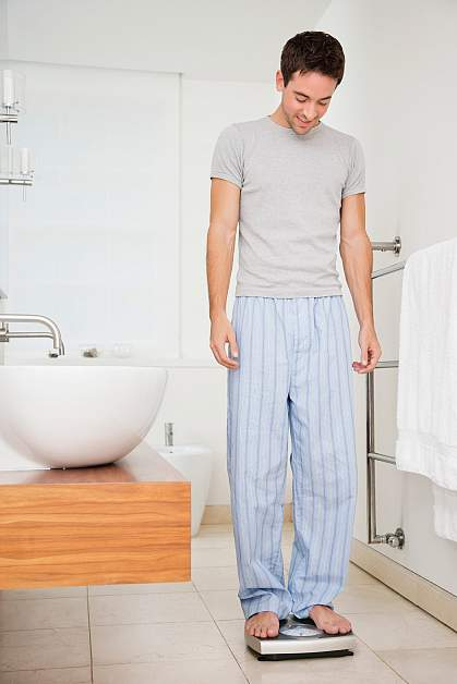 Photo of a slightly overweight man standing on a bathroom scale