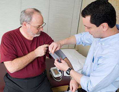 Photo of a doctor taking the blood pressure of an older man