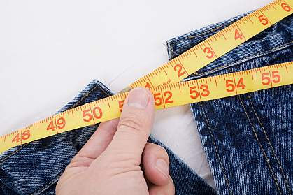 Photo of a person taking a waist measurement