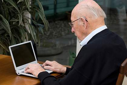 Photo of an older man using a laptop computer