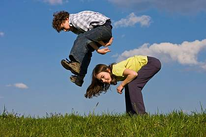 Photo of a boy and a girl playing leap frog