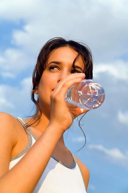Photo of a woman drinking from a hard plastic water bottle