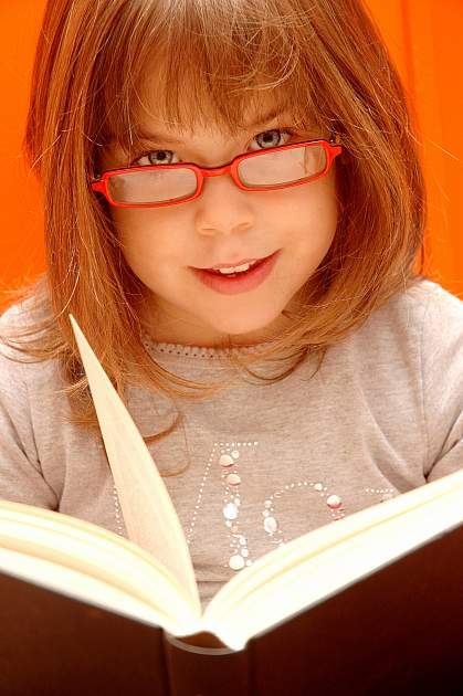 Photo of a young girl reading with glasses