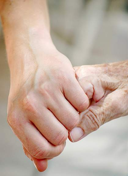 Photo of a young hand holding an elderly hand