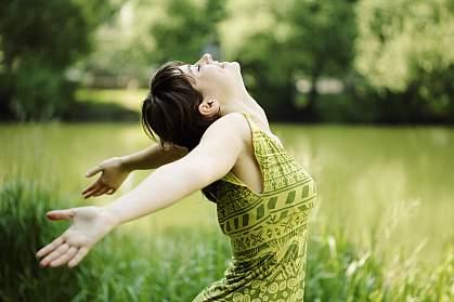Photo of joyful young woman in meadow