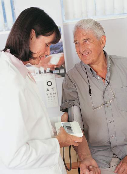 Photo of a female doctor checking the blood pressure of an older man