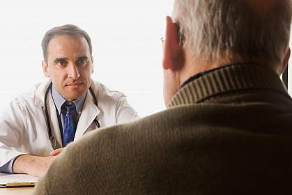 A photo of an older man consulting with his doctor