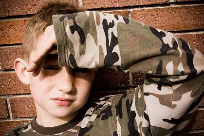 photo of a young boy shielding his eyes from a bright light