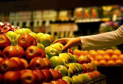 A photo of a hand picking up an apple at the supermarket