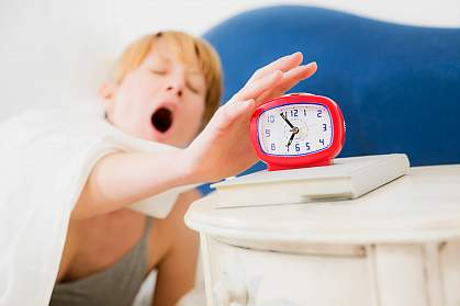 Photo of a sleepy woman reaching for her alarm clock