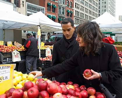 Photo of two people at an outdoor fruit stand