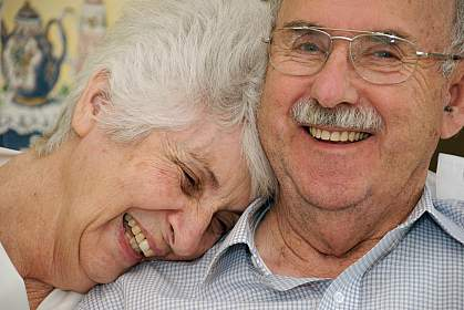 Photo of a happy senior couple, the woman with her head on his shoulder