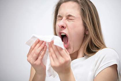 Photo of a young woman sneezing