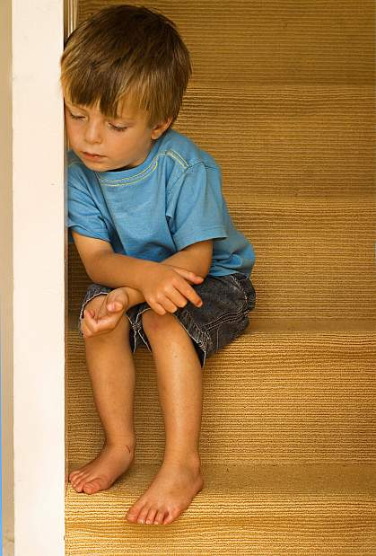 a photo of a young boy, looking down, seated on some stairs