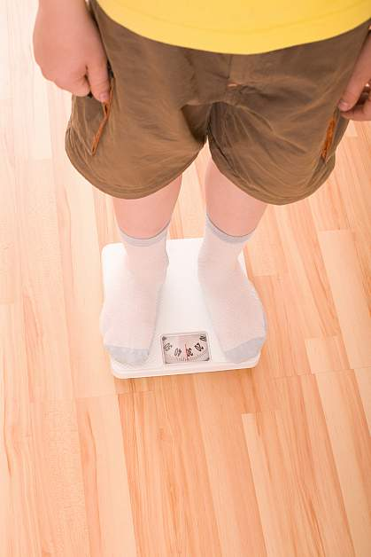 Photo of a boy standing on a bathroom scale