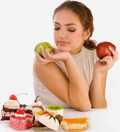 photo of a woman holding two apples but looking down at some sweets