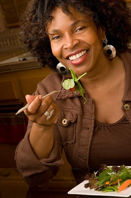 photo of a happy woman eating salad