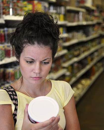 Woman reading a nutritional label.