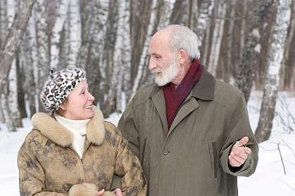 Photo of an older couple standing in the snow