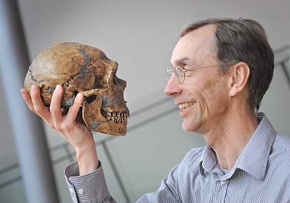 Photo of Dr. Svante Pääbo holding a Neanderthal skull