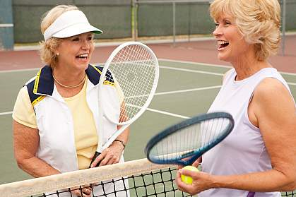 Photo of two older women playing tennis