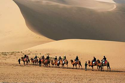 Photo of people riding camels past sand dunes