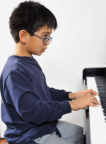 Photo of a boy playing a piano