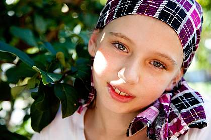 Photo of a young girl wearing a headscarf, smiling