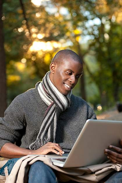 Photo of a young African-American man looking at a computer and smiling